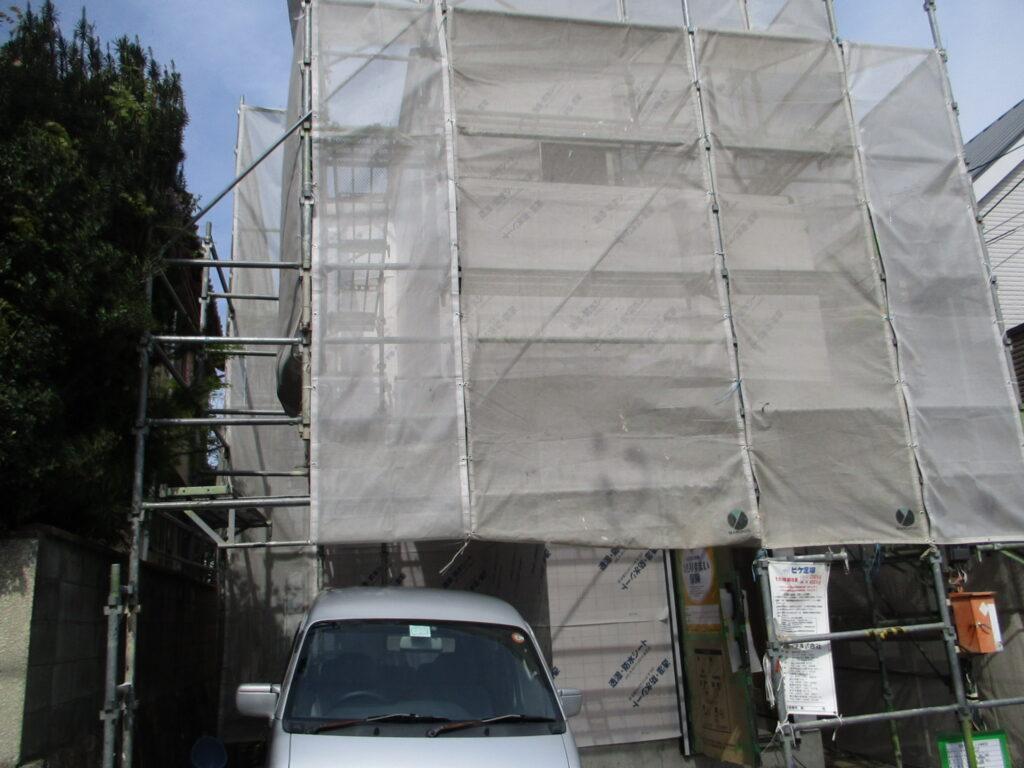 シートで覆われている建設中の新築物件